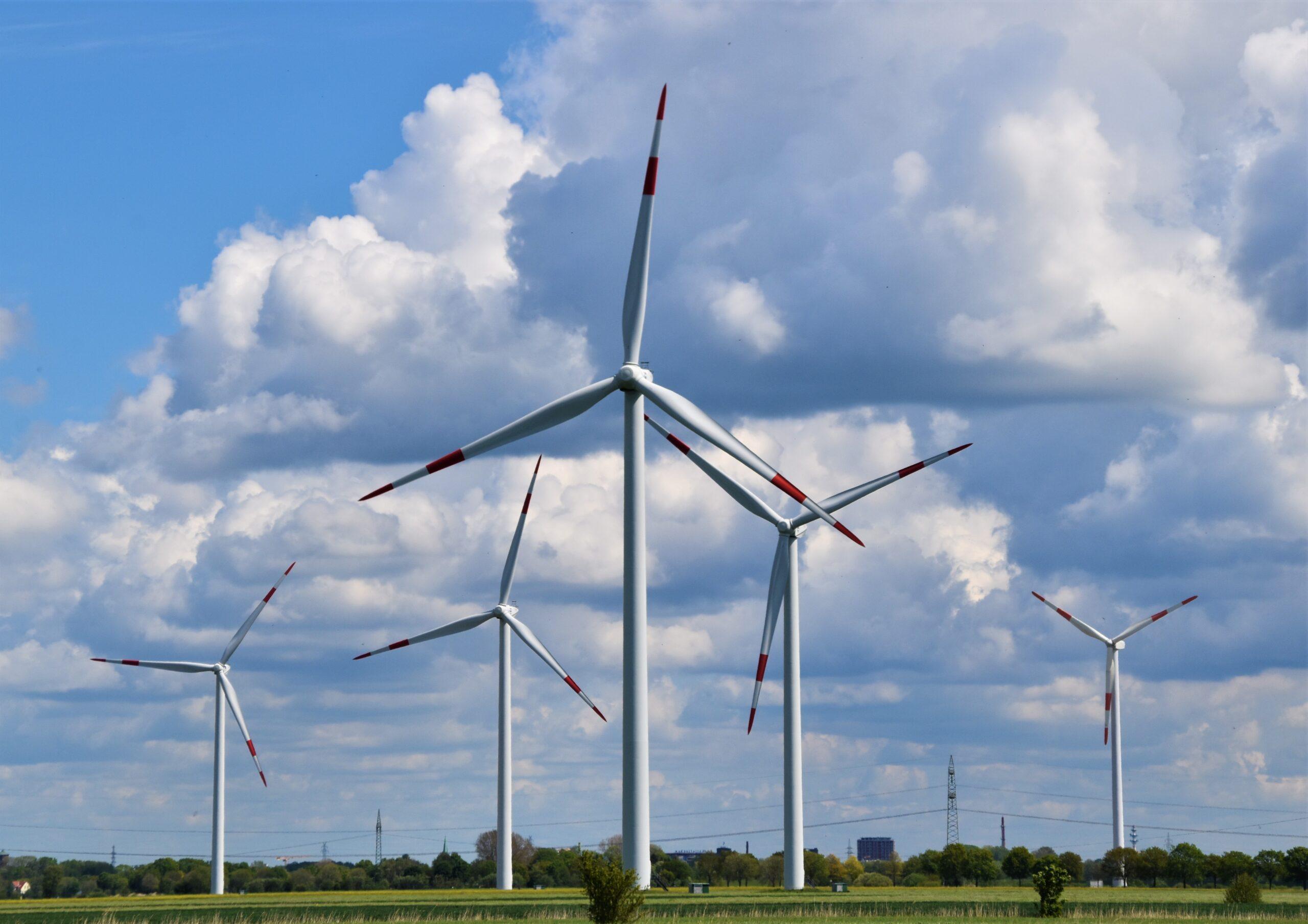 Tuulivoima. Tuulimyllypuisto kesällä, taustalla kumpupilviä